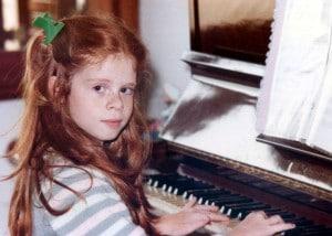 Fernanda ao piano com 8 anos